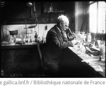 [Laboratoire avec fioles diverses, appareils de pesée, microscope... et homme assis] : [photographie de presse] / [Agence Rol]