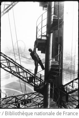 Tour Eiffel, peinture [peintre en équilibre sur un escalier de la Tour Eiffel] : [photographie de presse] / [Agence Rol]