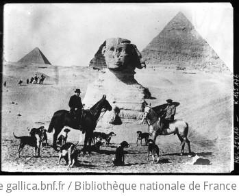 Egypte [deux cavaliers avec une meute de chiens au pied du Sphinx et des pyramides] : [photographie de presse] / [Agence Rol]