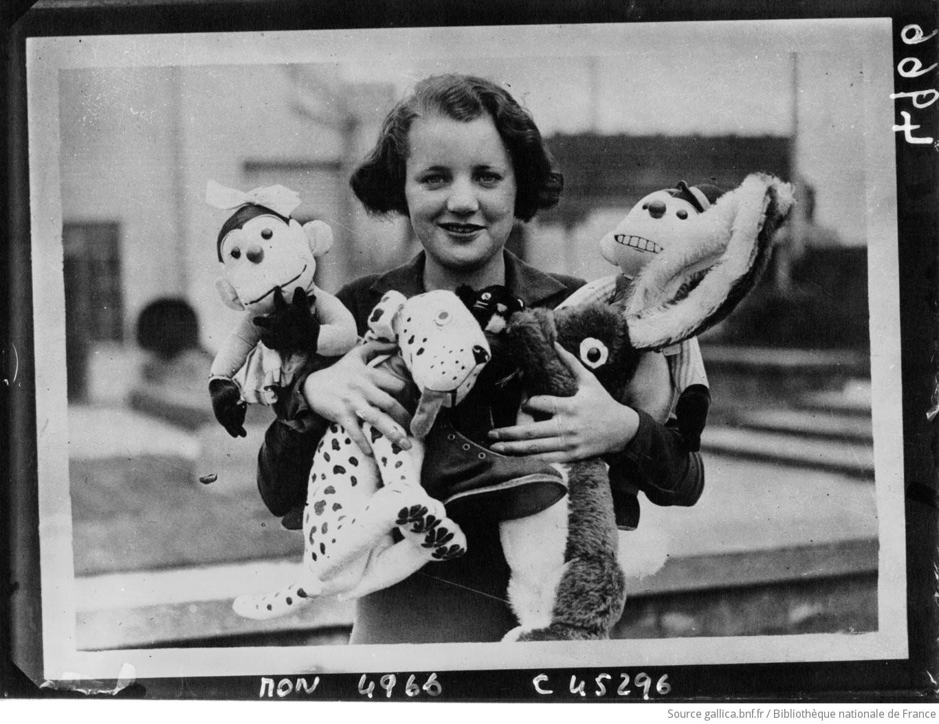 Jeune fille tenant des jouets pour la Noël. Source : BNF ©[photographie de presse]/Planet